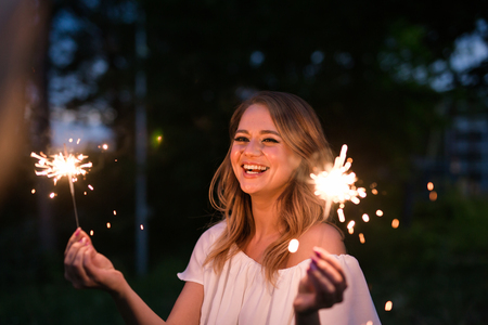 Portrait of young attractive celebrating woman holding sparkles Stock Photo