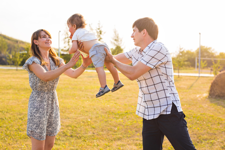 upbringing: Happy young family having fun outside in summer nature.