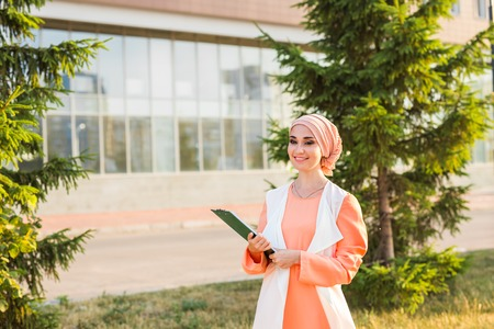 Arab Student holding a folder. Young beautiful Muslim woman walk in the city. Stock Photo