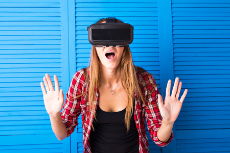 mediated: technology, virtual reality, entertainment and people concept - happy young woman with virtual reality headset or 3d glasses Stock Photo