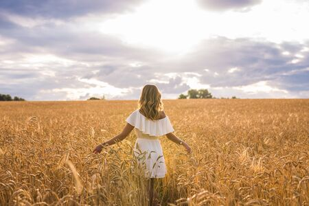 beatitude: Woman with arms outstretched in a wheat field.