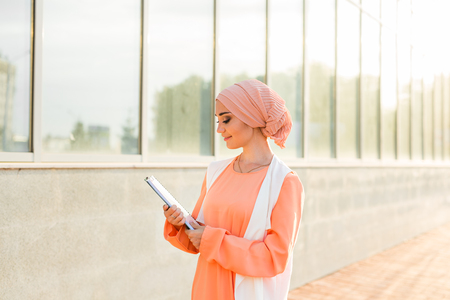 Young Muslim woman standing , holding document paper.