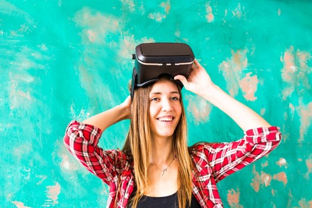 though: Young woman watching though the VR device.