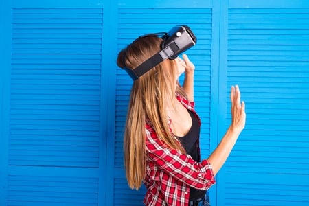 Smile happy woman getting experience using VR-headset glasses of virtual reality at home much gesticulating hands.