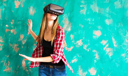 happy smiling young beautiful girl l getting experience using VR-headset glasses of virtual reality at home much gesticulating hands Imagens
