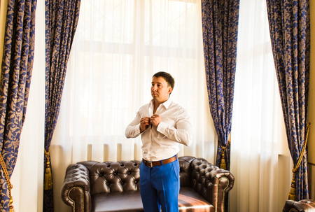 workday: Handsome man putting on shirt standing near window at his room in morning. Preparing for some event or new workday. New opportunities, dating, wedding day or getting ready for job interview concept Stock Photo