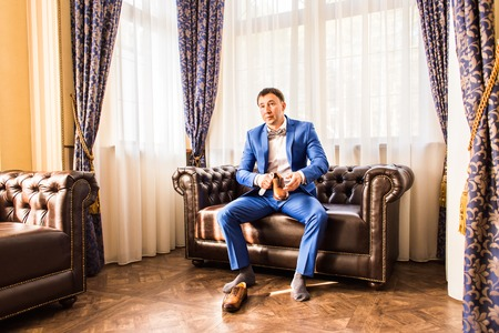 Handsome man putting on wedding shoes indoors Stock Photo