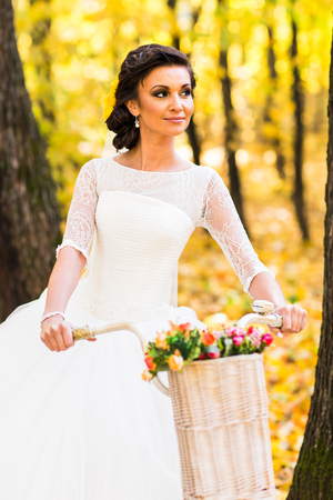 trash the dress: Bride on a bicycle in autumn nature. Stock Photo