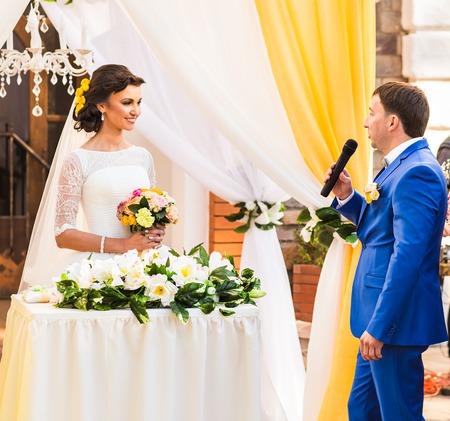 Elegantes recién casados ??sonrientes felices en la ceremonia de boda al aire libre de lujo. Foto de archivo - 62752263