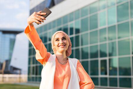 Muslim woman in hijab making selfie outdoors.