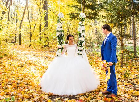 The bride and groom on a swing in autumn park. Stock Photo