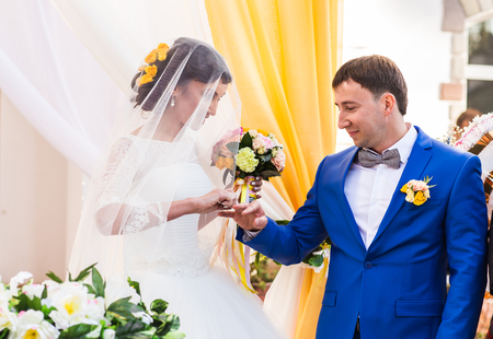 registry: Newlyweds exchange rings, groom puts the ring on the brides hand in marriage registry office