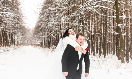 Groom giving piggyback ride to bride in winter woods. Stock Photo