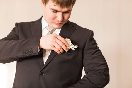boutonniere: colorful wedding boutonniere on suit of groom.