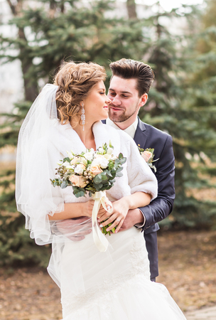 Newlyweds in autumn park, the groom embracing his bride Stock Photo