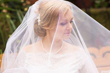 face of a beautiful bride hidden veil.