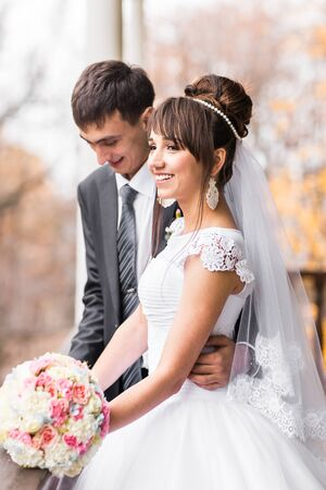 Bride and Groom walking in autumn park Stock Photo