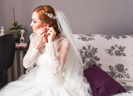 embellishment: Wedding earrings on a female hand, she takes the earrings, the bride fees, morning bride, white dress, wear earrings