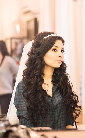 estilo de someterse al maquillaje novia hermosa en el salón de belleza de lujo con grandes espejos y luz Foto de archivo