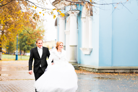 Bride and groom walking in the autumn or winter park. Stock Photo