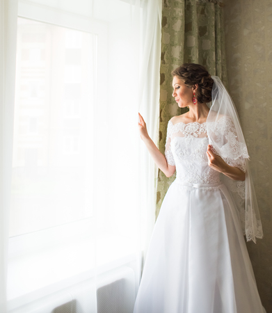 beautiful young bride standing beside a large window waiting