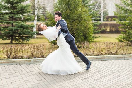 Young Wedding couple dancing in the park