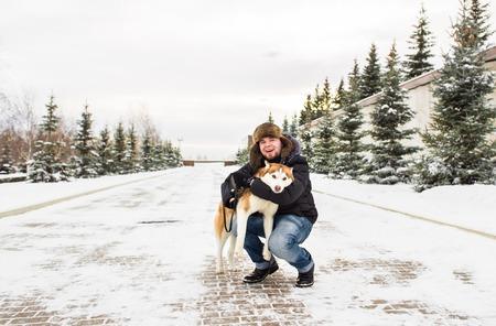 snowscene: Man and dog in snow. Man Walking Dog Through Snowy Woodland