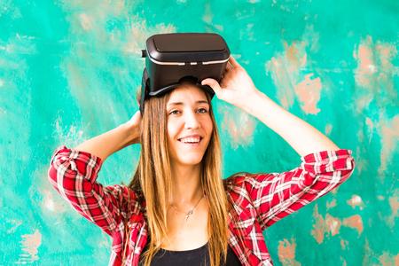 virtual reality simulator: Young Woman Wearing Virtual Reality Headset In Studio. Stock Photo