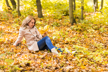 lying on leaves: woman lying on autumn leaves, outdoor portrait. Stock Photo