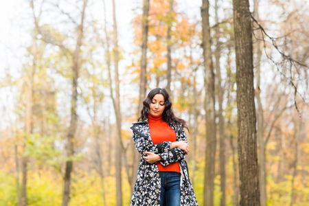 Autumn concept - Beautiful young modern woman walking in nature. Stock Photo