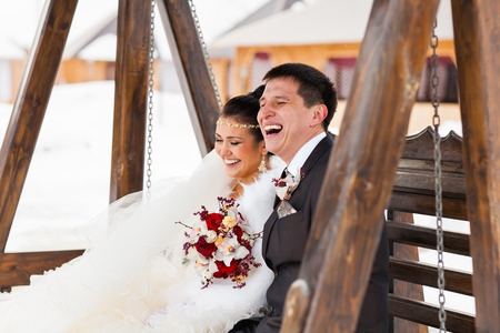 winter wedding: Bride and groom laughing on their winter wedding day .