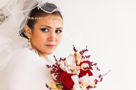 Young bride with the flower bouquet in winter time.