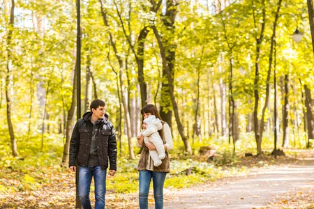 Young couple with newborn son outdoors in autumn.