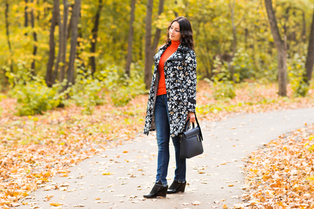 artsy: Street fashion concept - closeup portrait of a pretty girl. Wearing hat and suede jacket holding bag with fringe. Beautiful autumn woman. Artsy bohemian style. Outside, fall fashion Stock Photo