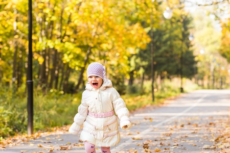 Little girl running the road in the autumn park
