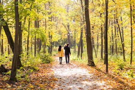Família nova feliz com sua filha passar tempo ao ar livre no parque do outono.