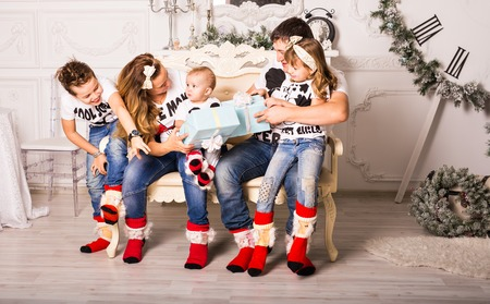Family exchanging gifts in front of Christmas tree Stock Photo