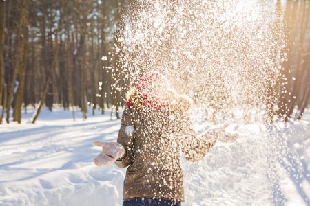 Beauty Girl Blowing Snow in frosty winter Park. Outdoors. Flying Snowflakes