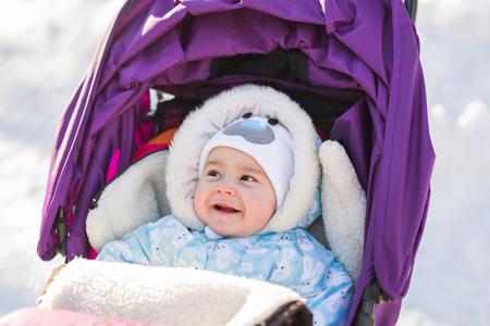 Funny laughing baby sitting in a stroller on c old winter day.