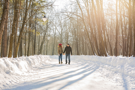 Couple holding each others hands, the winter goes on the road, enjoying a stroll, a love couple. Husband and wife are going through the park holding hands in the winter. The movement of people.
