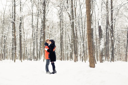 Young couple kissing on winter snowy day