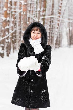 mittens: smiley pretty woman holding snow in mittens.