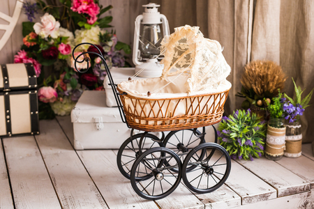 Dolls pram. Vintage doll stroller. Retro cart dolls made of rattan and white lace. Stock Photo