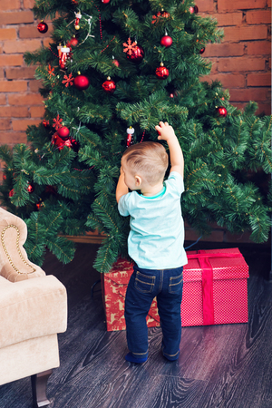 decorating christmas tree: Little boy decorating a Christmas tree toys