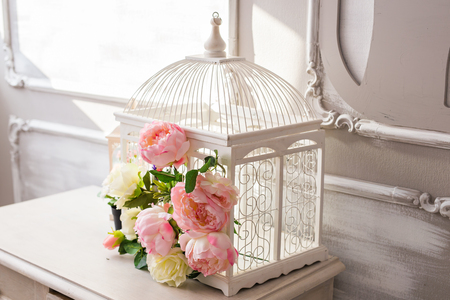 Shabby chic bird cage in interior. White cage