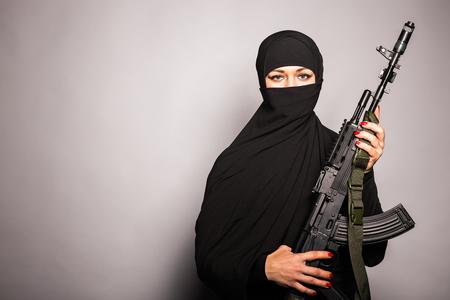 Moslim vrouw met een machinegeweer. Een gewapende vrouw schiet. Islamitische vrouw met een automatisch wapen. Concept van de oorlog en terrorisme.