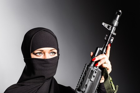 Muslim woman with a machine gun. An armed woman shoots. Islamic Woman holding an automatic weapon. Concept of war and terrorism.