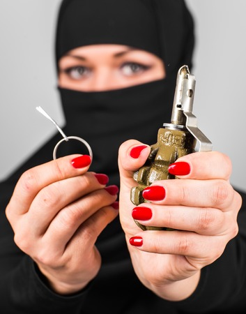 Hand grenade in a Eastern womans hand. The concept of terrorism and war.
