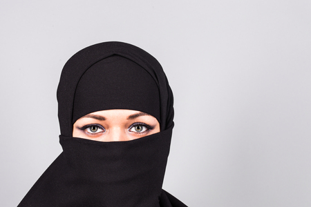 niqab: Beautiful girl wearing a niqab - grey background