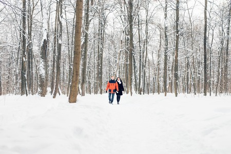 Young couple in love walking in the snowy forest.